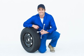 Mechanic leaning on tire while holding wheel wrenches