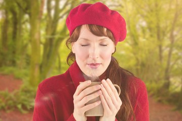 Composite image of woman holding a warm cup