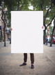 Man with blank poster on a street - 77374284