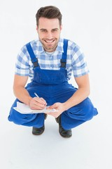 Happy repairman crouching while writing on clipboard