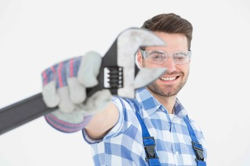 Handyman wearing protective glasses while holding wrench