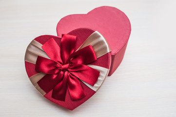 the holiday box in the shape of a heart with a bow on Valentine'