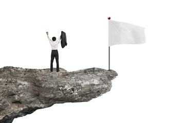 man cheering on cliff with blank flag and white