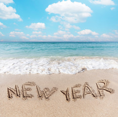 """New Year"" words written on the beach sand."