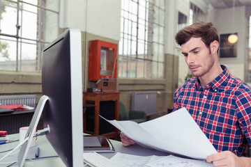mann im büro schaut konzentriert auf unterlagen