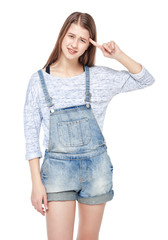 Young fashion girl in jeans overalls making crazy gesture isolat