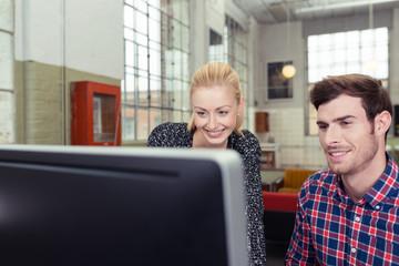 zwei junge leute schauen auf computer