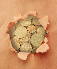 Golden coins through torn brown paper