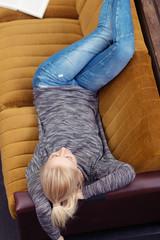 junge frau liegt auf dem sofa in ihrer wohnung