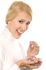 Smiling Beautiful Young Woman Eating Colorful Pills