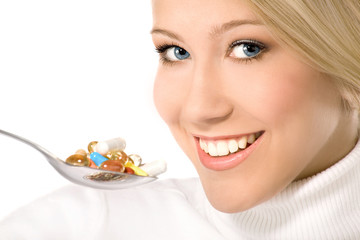 Smiling young woman eating a lot of pills on spoon