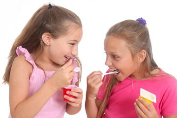 happy girls eating yogurt