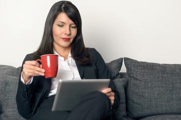 Attraktive Geschäftsfrau trinkt Kaffee und liest auf Tablet