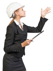 Businesswoman wearing hard hat, with clipboard and pen, pointing