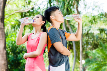 Asian couple drinking water after sport in park