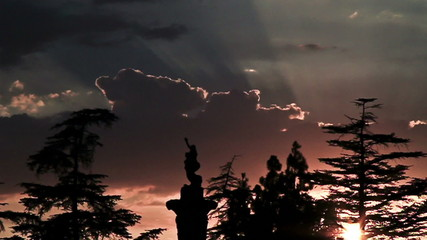 Dramatic sunset behind cemetery statues in time lapse