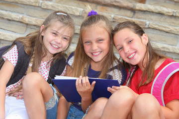 happy schoolgirls with a book outdoors