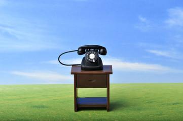 草原の中に置いてある黒い電話