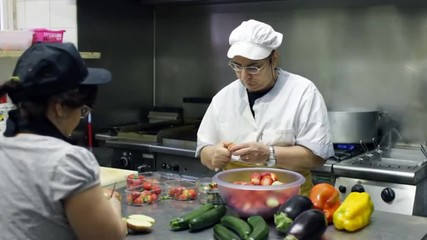 chef cook and cook's assistant cutting strawberry and vegetables