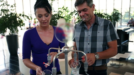 Close up shot of a young beautiful couple when pouring mineral water in special glass