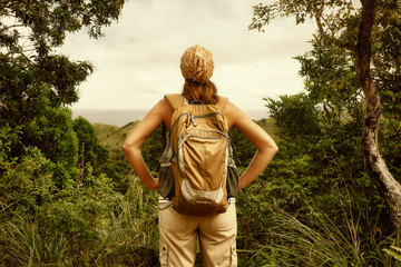 Young woman traveller with backpack in a woods.