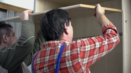 Guys place the shelf into the wardrobe