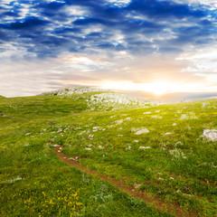touristic trail through a green hills scene