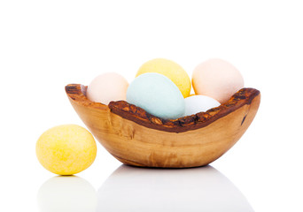 Easter eggs in wooden bowl, isolated on white background