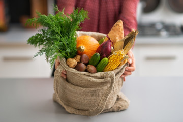 Closeup on housewife showing fresh vegetables in shopping bag