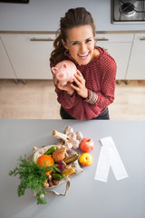 Happy young housewife showing piggy bank after shopping