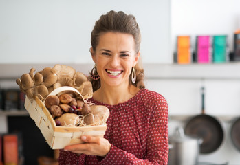 Portrait of smiling housewife showing basket with mushrooms