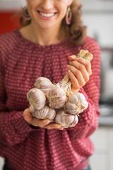 Closeup on young housewife showing bunch of garlic