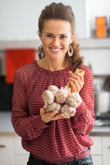 Portrait of smiling young housewife showing bunch of garlic
