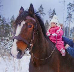 Baby girl horseback riding at winter