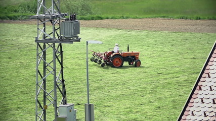 Farmer on tractor with electric tower in front