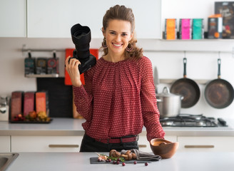 Portrait of smiling female food photographer in kitchen