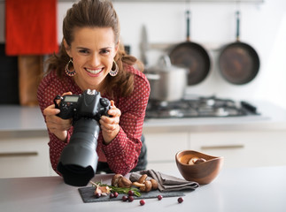 Portrait of happy female food photographer checking photos