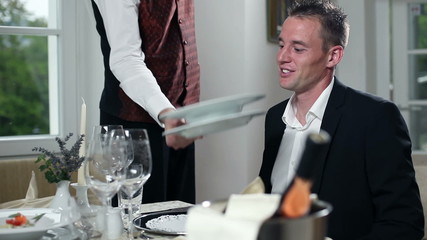 young man is served with dinner by the waiter inside beautifull restaurant with fancy plate settings and bottle of wine
