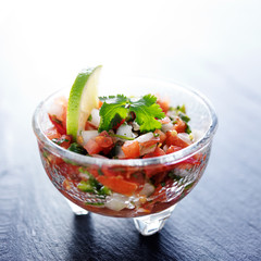 fresh pico de gallo salsa in glass bowl with lime