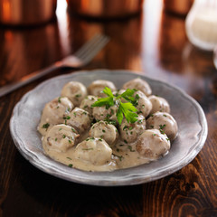 swedish meatballs with parlsey on wooden table