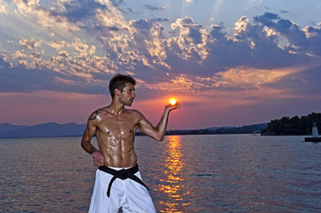 Man practicing martial arts on beach, hand cupping sun