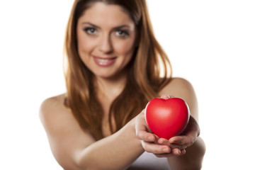 happy woman holds in her hand a heart shape object