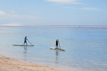 Cook Islands, Rarotonga, Two boys paddle boarding