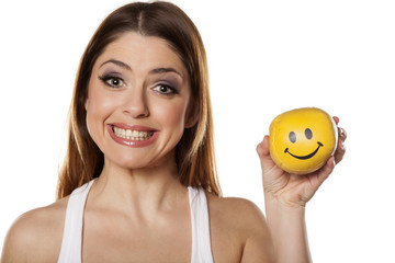 Happy woman holds in her hand a smiley ball