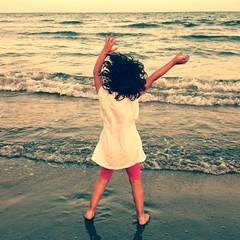 Niña bailando en la playa