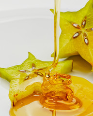 Studio shot of honey drizzling on slice of star fruit