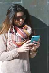 Young woman with winter clothes using smartphone