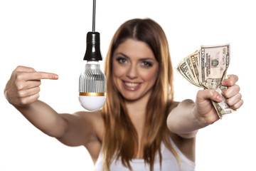 Smiling woman pointing on LED bulb, and holding wad of money
