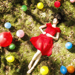 United Kingdom, England, Berkshire, Young woman with balloons sleeping in forest