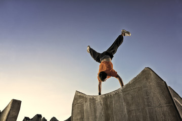 Man doing parkour handstand in urban setting